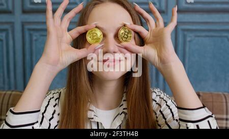 Femme freelance tenant deux pièces d'or à la maison, programmeur de développeur réussi, gagnant des bitcoins