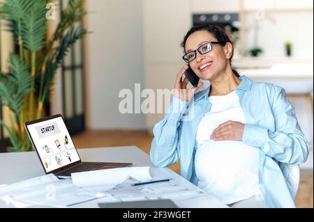 Bonne femme enceinte de race mixte est assise près de son bureau, ayant une agréable conversation d'affaires de téléphone cellulaire, touchant doucement son ventre, regardant loin et souriant