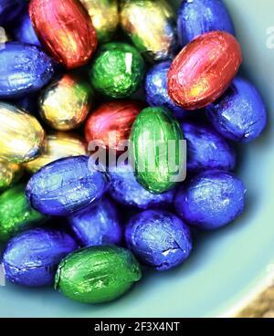 Œufs de Pâques au chocolat affichés dans de nombreuses couleurs sur fond blanc photo
