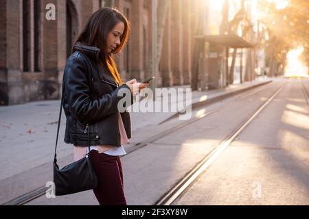 jeune femme textant sur son téléphone en traversant la rue, concept de communication et de style de vie urbain, espace de rédaction pour le texte