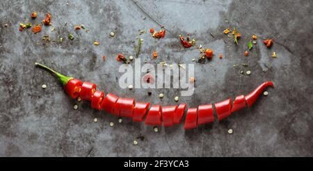 Des pods entiers et hachés de poivrons rouges sur fond sombre. Mise au point au centre de l'image.