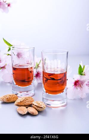 liqueur d'amande. La boisson traditionnelle forte en italie pour compléter le dîner est une liqueur à base de noix et de baies. Ratafia, alcool en grenaille. Sur la table et les amandes en fleurs. Vertical . Copier l'espace