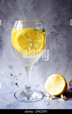 Citrons et un verre de limonade sur fond gris