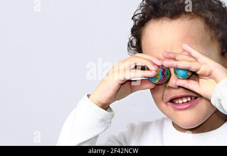Enfant avec des œufs de Pâques au chocolat dans de nombreuses couleurs photo d'arrière-plan blanche