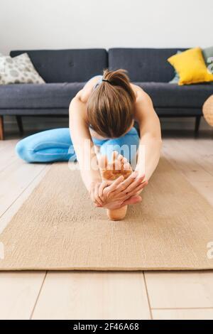 Portrait d'une jeune femme pratiquant le yoga à l'intérieur. Femme pratique janu sirsasana à la maison.
