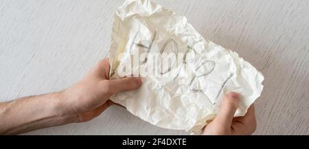 personne mains tenant une feuille de papier avec le mot d'espoir