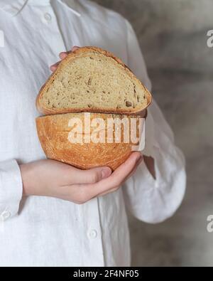 La boulangère femelle tient du pain bio artisanal fait maison, frais du four. Pain au levain maison. Plats faits maison. Préparation des aliments.