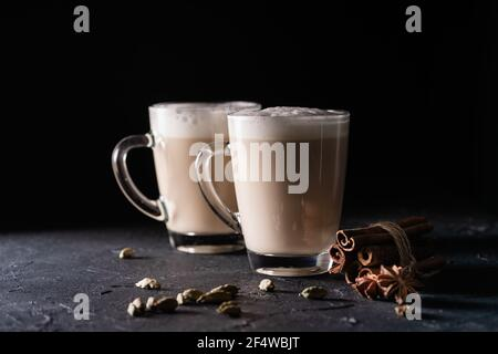 Deux tasses de thé Chai Latte, boisson chaude au thé avec lait mousse sur fond noir foncé