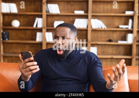 Un homme afro-américain choqué tenant un smartphone, se sent étonné d'une mauvaise nouvelle, renvoyé du travail, un homme irrité regarde l'écran du téléphone et ne comprend pas ce qui s'est passé