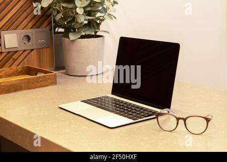 Lieu de travail dans l'appartement ou le café avec intérieur moderne. Ouvrez l'ordinateur portable et les lunettes sur la table. Concept d'entreprise, travail à distance depuis la maison, apprentissage à distance
