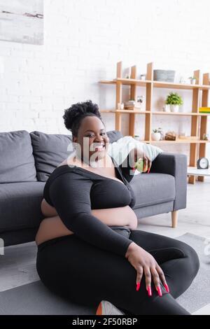 joyeux afro-américain femme de taille plus dans les vêtements de sport tenant vert apple