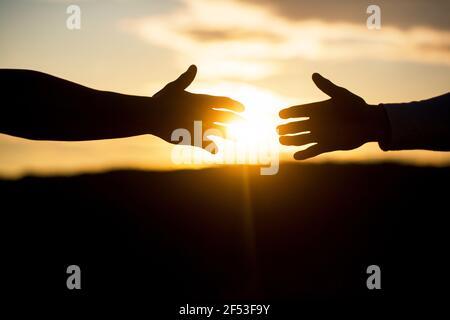 Poignée de main amicale, salutation des amis, travail d'équipe, amitié. Sauvetage, geste d'aide ou mains. Mains étirées, salut, silhouette d'aide, concept