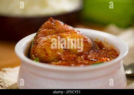 Seer curry de poisson, curry traditionnel de poisson indien, kerala spécial, arrangé dans un bol blanc avec un bol de riz cuit et feuille de banane pour servir la nourriture, un