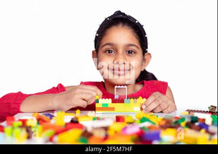 Une petite fille indienne mignonne jouant avec des blocs de construction de jouets colorés et s'amusant. Concept d'activité de développement des enfants. Apprentissage au début de l'école