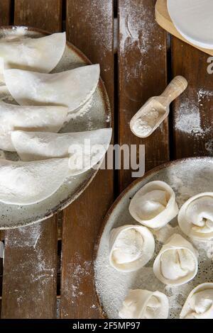 Boulettes faites maison crues sur deux assiettes sur une table en bois sombre.