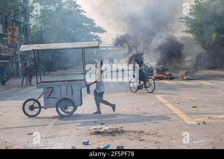 Un cycliste passe devant des pneus en feu dans la rue lors d'une manifestation contre le coup d'État militaire.la police et les militaires du Myanmar (tatmadow) ont attaqué les manifestants avec des balles en caoutchouc, des munitions réelles, des gaz lacrymogènes et des bombes lacrymogènes en réponse aux manifestants anti-coup d'État militaire de samedi, tuant plus de 90 personnes et en blessant beaucoup d'autres. Au moins 300 personnes ont été tuées au Myanmar depuis le coup d'État du 1er février, a déclaré un responsable des droits de l'homme de l'ONU. L'armée du Myanmar a détenu le conseiller d'État du Myanmar Aung San Suu Kyi le 01 février 2021 et a déclaré l'état d'urgence tout en prenant le pouvoir