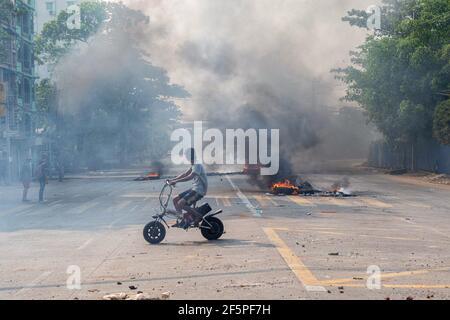 Un automobiliste passe devant des pneus en feu dans la rue lors d'une manifestation contre le coup d'État militaire.la police et les militaires du Myanmar (tatmadow) ont attaqué les manifestants avec des balles en caoutchouc, des munitions vivantes, des gaz lacrymogènes et des bombes lacrymogènes en réponse aux manifestants anti-coup d'État militaire de samedi, tuant plus de 90 personnes et en blessant beaucoup d'autres. Au moins 300 personnes ont été tuées au Myanmar depuis le coup d'État du 1er février, a déclaré un responsable des droits de l'homme de l'ONU. L'armée du Myanmar a détenu le conseiller d'État du Myanmar Aung San Suu Kyi le 01 février 2021 et a déclaré l'état d'urgence en s'emparant de la puissance
