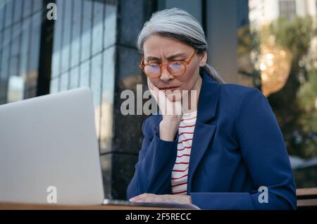 Femme d'affaires asiatique fatiguée travaillant projet, utilisant un ordinateur portable, recherche d'informations. Portrait d'une femme mûre frustrée assise sur le lieu de travail
