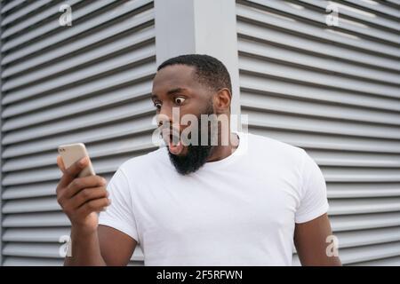 Choqué l'homme américain africain avec la bouche ouverte en utilisant le téléphone mobile regardant l'écran numérique. Un gars stupéfait de regarder des nouvelles en ligne