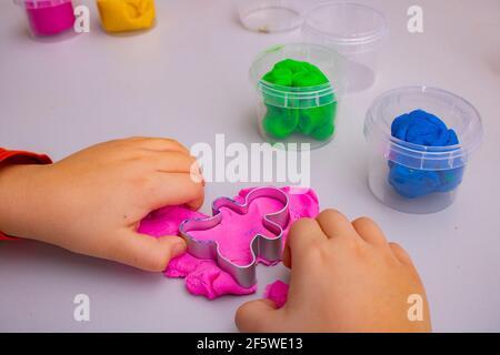 Un enfant jouant avec de l'argile colorée, vue de dessus