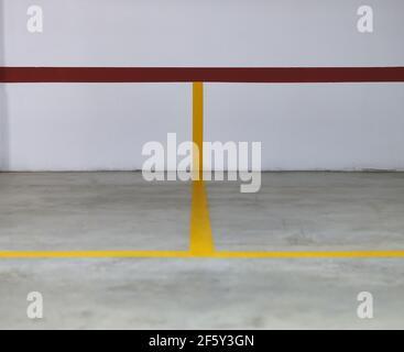 détail de certaines lignes jaunes et rouges sur un mur et un sol en béton qui délimite certaines places de stationnement