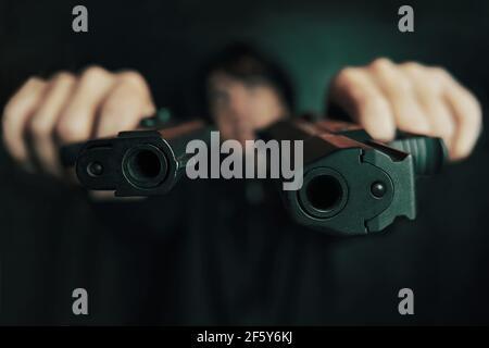 Gros plan de deux muzzles de canon. Guy menace avec une arme à feu. Deux pistolets dans les mains de l'homme sont pointés à la caméra. Criminel avec arme. Banque D'Images
