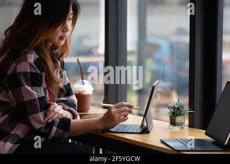 Jeune créateur tenant le stylet dessin à l'écran de tablette numérique au café