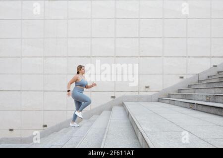 Déterminé taille plus jeune femme courir dans les escaliers à l'extérieur, s'entraîner en ville et atteindre le concept de but