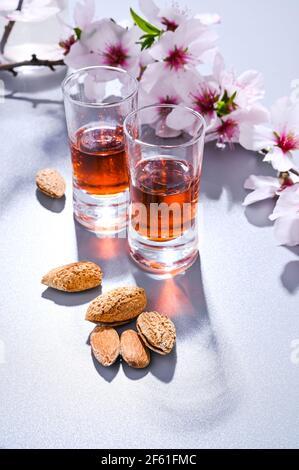 liqueur d'amande. La boisson traditionnelle forte en italie pour compléter le dîner est une liqueur à base de noix et de baies. Ratafia, alcool en grenaille. Vue de dessus sur la table et amandes en fleurs. Copier l'espace