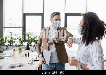 partenaires d'affaires interraciaux dans les masques médicaux faisant le coude salutation dedans bureau Banque D'Images