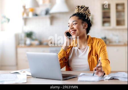 Heureux réussi occupé jeune afro-américain femme, courtier, gestionnaire ou indépendant travaillant à distance, ont agréablement conversation avec le client ou employé au téléphone en regardant loin sourire amical