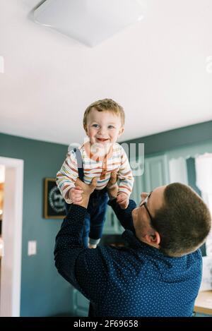 père levant son bébé garçon en train de rire debout dans son cuisine Banque D'Images