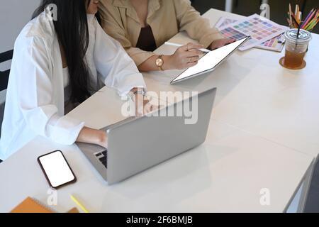 Une jeune femme designer montre quelque chose sur une tablette numérique à sa collègue pendant qu'elle est assise dans un bureau créatif.