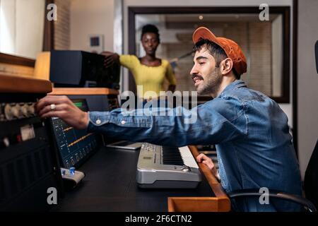 Photo de la bonne femme noire en studio de musique et producteur de sexe masculin utilisant un clavier de piano électronique.