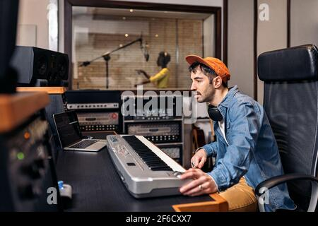Photo d'un producteur de musique masculin travaillant avec un chanteur noir dans un studio de musique cool.