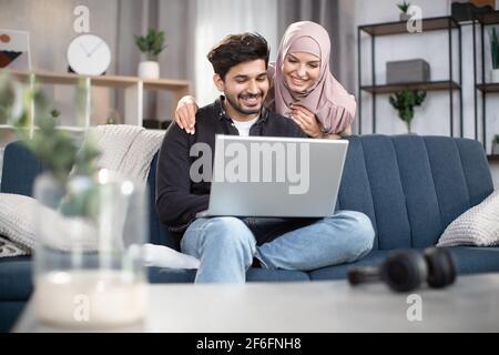 Jeune homme arabe beau barbu assis sur le canapé et regardant un film ou des informations sur un ordinateur portable à la maison, tandis que sa jolie femme souriante dans le hijab, debout derrière lui et regardant l'écran.