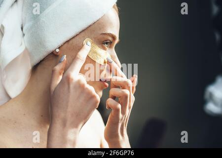 La femme caucasienne se concentre sur l'application de cellules oculaires hydrogel sous les yeux à la maison ayant une journée au spa