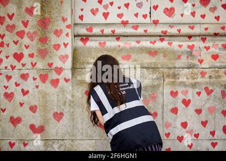 Londres, Royaume-Uni - 31 mars 2021 : la famille et les amis des victimes de Covid-19 peignent des coeurs rouges au mur commémoratif national de Covid, en face de l'hôpital St. Thomas, dans le centre de Londres. Chaque cœur tiré individuellement représente une victime du coronavirus.
