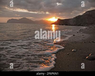 coucher de soleil rouge épique sur la plage, silhouettes de montagnes et ciel nuageux. Photo de haute qualité