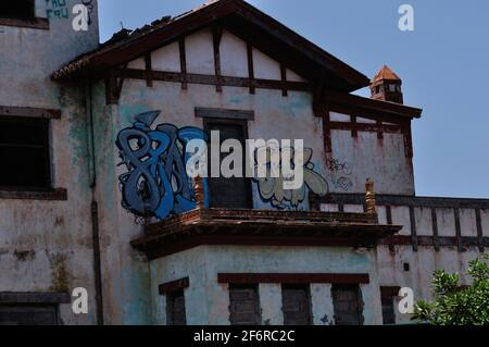 les artistes graffiti peignent dans une ancienne maison abandonnée