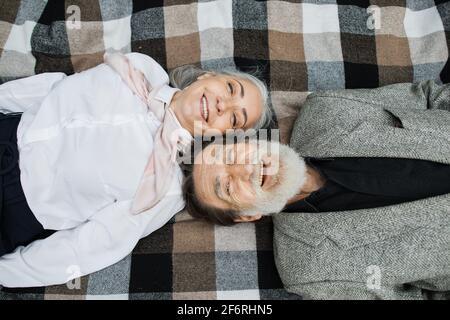 Vue de dessus d'un couple d'âge mûr caucasien allongé tête à tête sur une couverture à damier et souriant sur l'appareil photo. Bonne retraite. Amour pour les âges.
