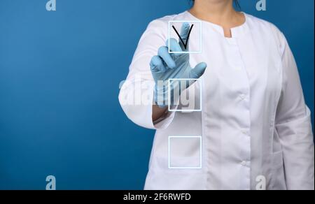 femme médecin sous un manteau médical blanc, gants en latex bleu sur fond bleu, touches de main et notes dans la liste sur un écran virtuel.