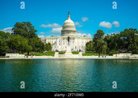 Le bâtiment du Capitole des États-Unis et les arbres se reflètent dans la piscine du Capitole lors d'une journée d'été ensoleillée à Washington, D.C.