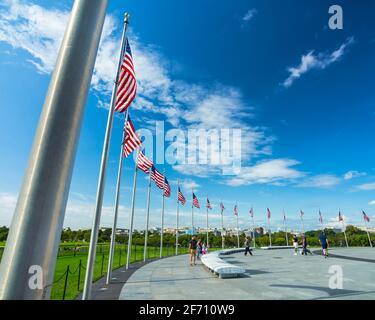 Une rangée de drapeaux américains sur les mâts de drapeaux soufflent dans le vent autour du Washington Monument à Washington, D.C., un jour ensoleillé