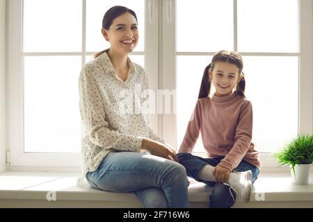Portrait de la jeune mère heureuse et de la petite fille seuil de fenêtre à la maison