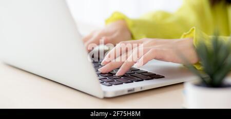 Gros plan de la main jeune femme d'affaires asiatique travaillant sur un ordinateur portable sur un bureau à domicile, freelance regardant et tapant sur un ordinateur portable sur une table, femme