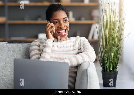 Bureau à domicile. Femme indépendante noire utilisant un téléphone portable et un ordinateur portable dans le salon.