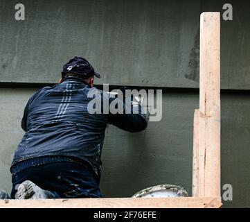 Dnepropetrovsk, Ukraine - 03.30.2021: Ouvrier de façade plâtrage mur extérieur de bâtiment.