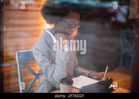 Jeune femme africaine concentrée en costume d'affaires écrivant des notes tout en étant assise à table de café avec une tablette numérique. Concept de travail à distance, personnel et technologie.