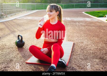 Une femme de fitness souriante boit de l'eau à partir d'une bouteille en verre réutilisable tout en prenant le repos assis sur un tapis dans le stade pendant l'entraînement en plein air. Actif